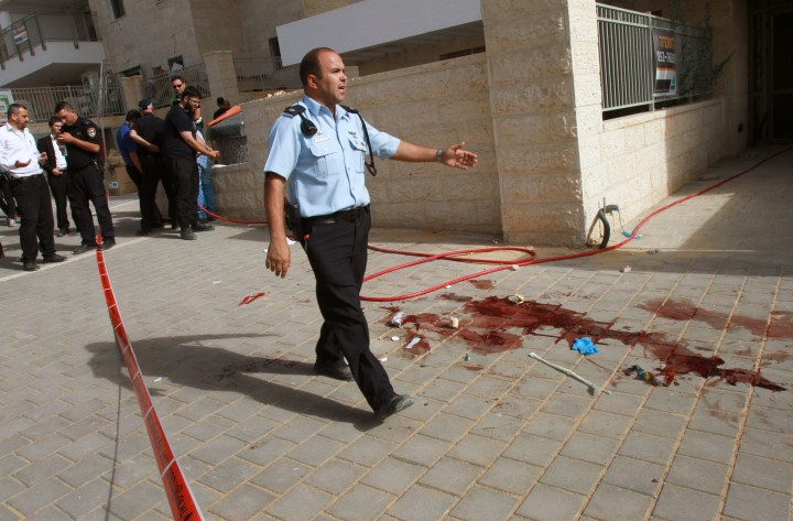 2015-10-22 13:27:43 Israeli police inspect the site where two alleged Palestinian attackers were shot by Israeli police after attempting to board a bus carrying children then stabbing an Israeli, in the Israeli city of Beit Shemesh, west of Jerusalem, on October 22, 2015. The two men were blocked from entering the bus in Beit Shemesh by the driver and others. They then stabbed and moderately wounded a 25-year-old Israeli man near the bus station, according to police spokesman Micky Rosenfeld. AFP PHOTO / GIL COHEN-MAGEN
