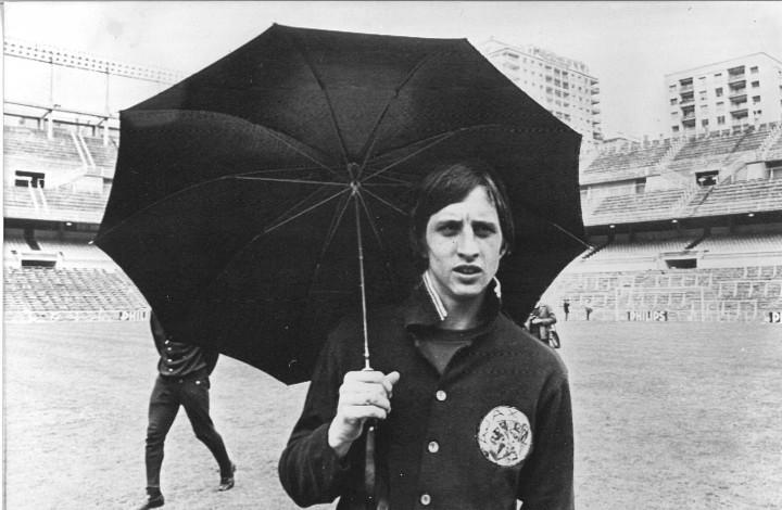 1969-05-27 12:00:00 Johan Cruijff onder de paraplu tijdens een vluchtige verkenning van het veld in het Bernabeu-stadion. Het klimaat was, toen de foto werd gemaakt, erg 'Hollands'./Johan Cruyff onder de paraplu tijdens een vluchtige verkenning van het veld in het Bernabeu-stadion. Het klimaat was, toen de foto werd gemaakt, erg 'Hollands'.