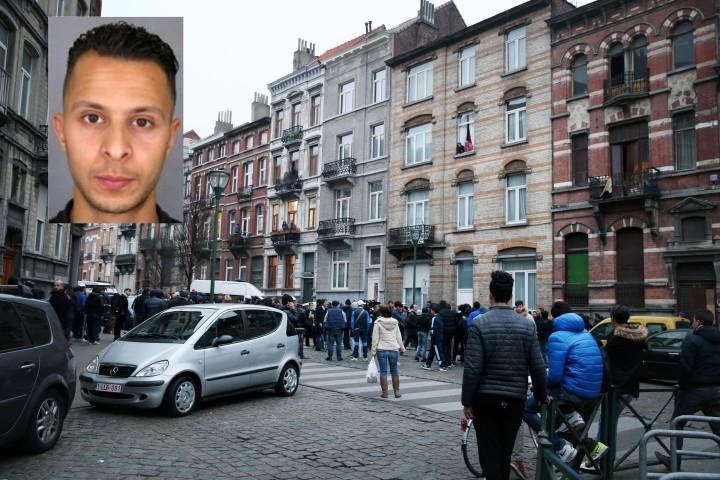 Abdeslam met op de achtergrond het appartement in Molenbeek waar hij zich maandenlang schuilhield - Foto: AFP