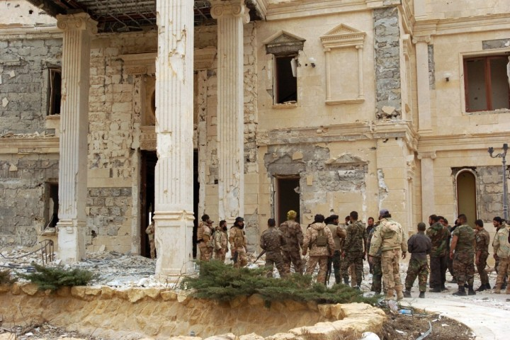 "2016-03-24 00:00:00 CORRECTION - Syrian troops stand next to a mansion belonging to the Qatari royal family on the outskirts of the ancient city of Palmyra on March 24, 2016. Backed by Russian warplanes and allied militia on the ground, the Syrian army advanced into Palmyra after launching a desert offensive early this month, said the Syrian Observatory for Human Rights. / AFP PHOTO / STR / ""The erroneous mention[s] appearing in the metadata of this photo by STR has been modified in AFP systems in the following manner: [on the outskirts of the ancient city of Palmyra] instead of [in the ancient city of Palmyra]. Please immediately remove the erroneous mention[s] from all your online services and delete it (them) from your servers. If you have been authorized by AFP to distribute it (them) to third parties, please ensure that the same actions are carried out by them. Failure to promptly comply with these instructions will entail liability on your part for any continued or post notification usage. Therefore we thank you very much for all your attention and prompt action. We are sorry for the inconvenience this notification may cause and remain at your disposal for any further information you may require."""