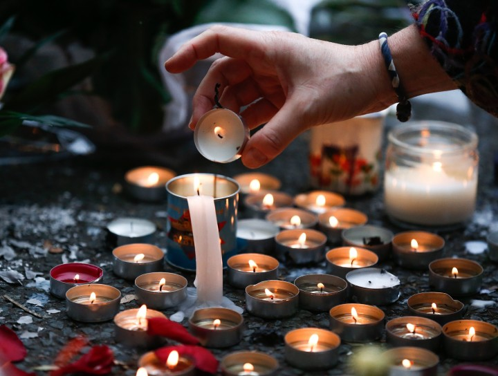 2015-11-14 17:20:51 epa05025285 A woman burns candles aside of a blood stain in a location near the Bataclan concert venue in Paris, France, 14 November 2015. More than 120 people have been killed in a series of attacks in Paris on 13 November, according to French officials. French President Francois Hollande says that the attacks in Paris were an 'act of war' carried out by the Islamic State extremist group. EPA/LAURENT DUBRULE