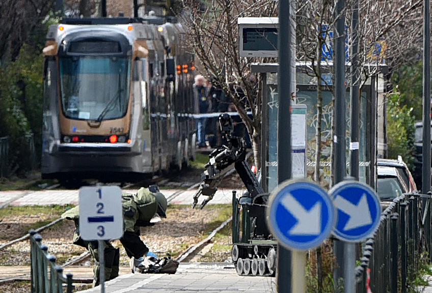 2016-03-25 15:49:57 An agent of a bomb squad unit action touches a suspicious object next to a bomb squad robot at a tramway station on March 25, 2016 in Schaerbeek suburb, Brussels, during a bomb alert as Belgian police arrested a suspect in a fresh anti-terrorist operation. A French police source said the raids in the Brussels suburb of Schaerbeek were related to the arrest of 34-year-old Reda Kriket in Paris on March 24, who was found with heavy weapons and explosives in his apartment. / AFP PHOTO / PATRIK STOLLARZ