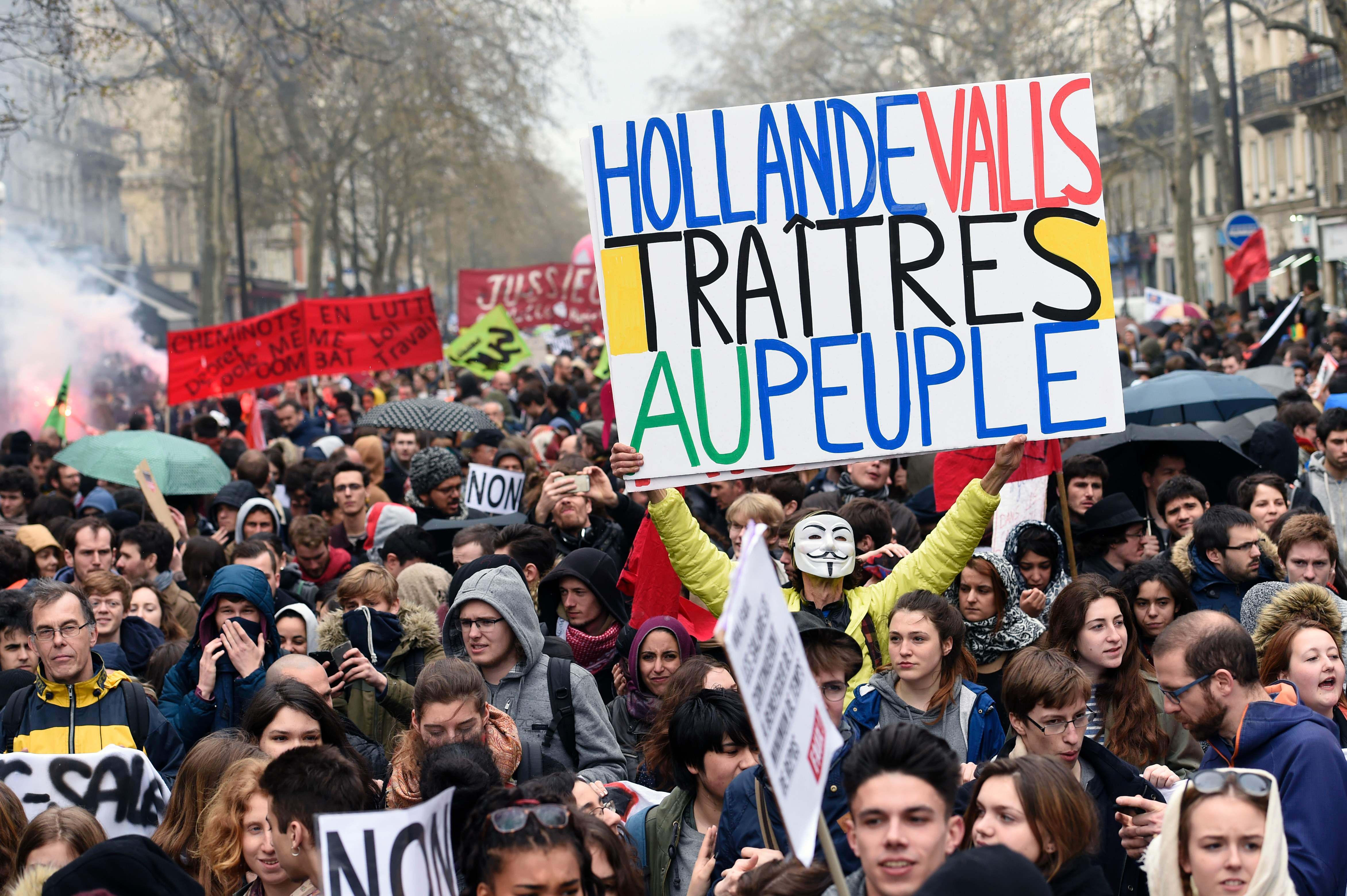"""2016-04-09 15:21:46 TOPSHOT - Protester Jean-Baptiste Redde aka Voltuan (C-R) holds up a placard reading """"Hollande, Valls, traitors to the people"""" in reference of French President Francois Hollande and French Prime Minister Manuel Valls, during a protest on April 9, 2016 in Paris, against the French government's proposed labour law reforms. AFP PHOTO / MIGUEL MEDINA / AFP PHOTO / MIGUEL MEDINA"""