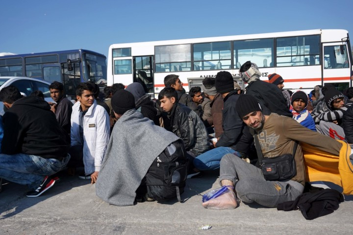 2016-03-29 10:00:39 Migrants and refugees wait to board buses taking them to the registration hotspot of Moria, from the port of Mytilene on the Greek island of Lesbos on March 29, 2016, after they were rescued by Frontex and Greek coast guards. The United States will provide an additional $20 million (18 million euros) in aid for refugees in Europe, a senior US official said on March 28, 2016. Most of the funds -- $17.5 million -- will be given to the UN refugee agency, Higginbottom said during a visit to Lesbos, the island that has experienced most of the refugee arrivals registered in Greece since 2015, where there are over 2000 refugees and migrants according to the Greek government. / AFP PHOTO / -