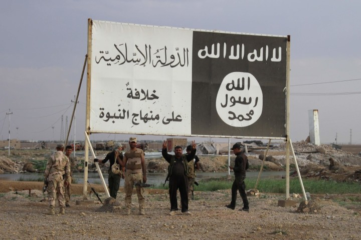 Iraqi government forces gather under a billboard bearing slogans of the Islamic State (IS) group and its trademark flag, in the town of Heet, in Iraq's Anbar province, which they are battling to retake from IS jihadists, on April 7, 2016. Earlier in the month Iraqi security forces recaptured parts of Heet, which was one of the largest population centres in Anbar province still held by the Islamic State (IS) group, but other areas remain under jihadist control. / AFP PHOTO / MOADH AL-DULAIMI