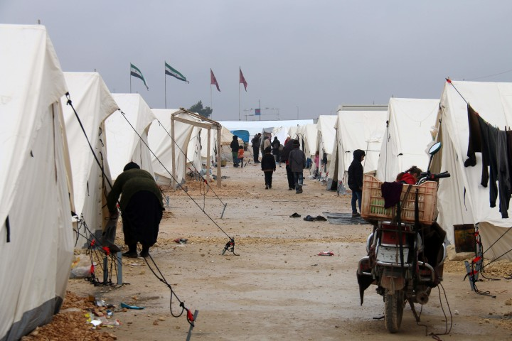 2016-02-12 13:52:26 Displaced Syrians fleeing areas in the northern embattled province of Aleppo, walk past tents at the Bab al-Salama camp, set up outside the Syrian city of Azaz on Syria's northern border with Turkey on February 12, 2016. / AFP / MUJAHED ABUL JOUD