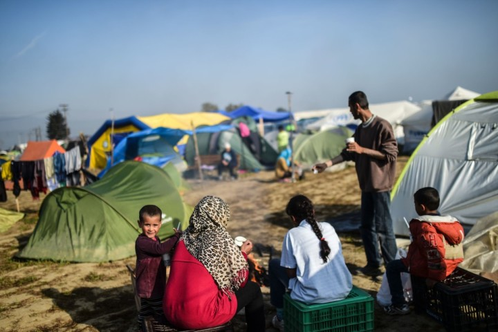 Migrants sit by a bonfire at their makeshift camp at the northern village of Idomeni, at the Greek-Macedonian border, on April 5, 2016. An enormous and complex logistical operation involving thousands of EU and other officials was launched on April 4 to ship migrants from Greece back to Turkey under a controversial accord between Brussels and Ankara. In the first wave of deportations, around 200 mostly economic migrants from Pakistan, Bangladesh and other countries were sent back to Turkey aboard chartered Turkish ferries sailing from the Greek islands of Lesbos and Chios. / AFP PHOTO / BULENT KILIC