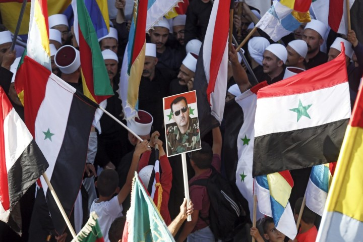 2015-06-15 14:24:03 epa04801151 Druze from the border village of Majdal Shams in the Golan Heights, near the Israeli-Syrian border, hold a poster of Syrian President Bashar al-Assad and Druze flags during a demonstration in support of their Syrian Druze brothers in Majdal Shams, Israel, 15 June 2105. The Druze community is calling for international support of the Syrian Druze minority after dozens were killed by Islamic extremists in northern Syria. The Syrian al-Qaeda affiliate al-Nusra Front, which has played a key role in recent rebel victories, has killed 20 villagers from the Druze religious minority in a north-western Syrian village, local residents and activists said 11 June 2015.  EPA/ATEF SAFADI