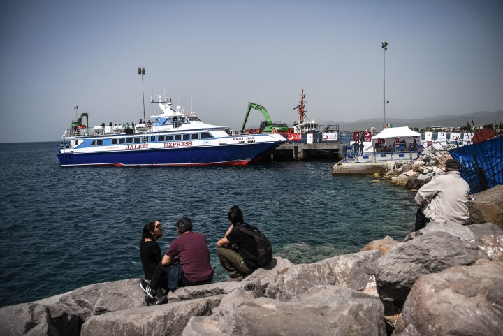 2016-04-08 12:43:56 People look on a Turkish ferry carrying second group of migrants deported from Greece to Turkey at the port of Dikili district in Izmiras on April 8, 2016. Greece deported a second batch of more than a hundred migrants to Turkey today under a controversial deal to stem mass migration as Germany announced a sharp drop in asylum claims. Police sources said a first boat left the Greek island of Lesbos carrying 45 Pakistani men, while a second carried 79 migrants, also mainly Pakistanis, back across the Aegean Sea where hundreds have lost their lives in a quest to reach Europe.   / AFP PHOTO / OZAN KOSE