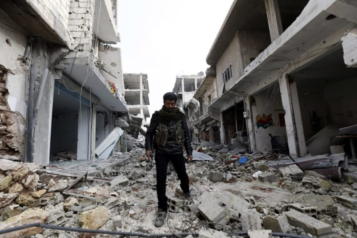 2015-01-28 14:01:02 epa04590715 A member of Syrian Kurdish People's Defence Units (YPG) walks through rubbles at a street in Kobane, Syria, 28 January 2015. According to reports Kurdish fighters on 26 January claimed to have pushed militants from the group calling themselves the Islamic State (IS) out of the embattled Syrian town of Kobane, following four months of fighting, which included airstrikes carried out by an international anti-IS coalition. EPA/SEDAT SUNA