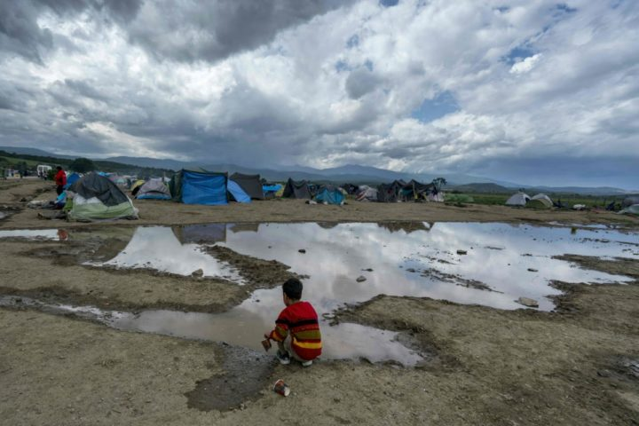 A boy plays by a pond at a makeshift camp for migrants and refugees near the village of Idomeni not far from the Greek-Macedonian border on April 25, 2016. Some 54,000 people, many of them fleeing the war in Syria, have been stranded on Greek territory since the closure of the migrant route through the Balkans in February. / AFP PHOTO / JOE KLAMAR