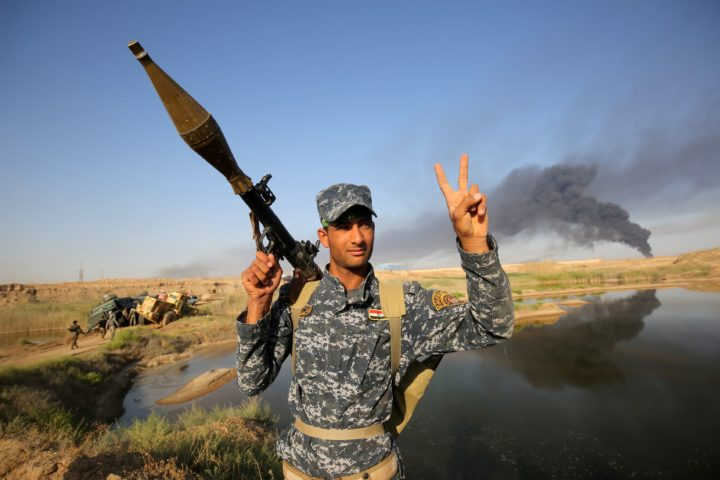 2016-05-23 19:01:33 A member of the Iraqi pro-government forces gestures as smoke billows in the background during an advance towards the city of Fallujah on May 23, 2016, as part of a major assault to retake the city from Islamic State (IS) group. Iraqi forces, consisting of special forces, soldiers, police, militia forces and pro-government tribesmen, launched a major assault to retake Fallujah, the scene of deadly battles during the US occupation and one of the toughest targets yet in Baghdad's war on the Islamic State group. Prime Minister Haider al-Abadi, commander-in-chief of the armed forces, announced the start of operations in the middle of the night and then visited the battle's operations room. / AFP PHOTO / AHMAD AL-RUBAYE