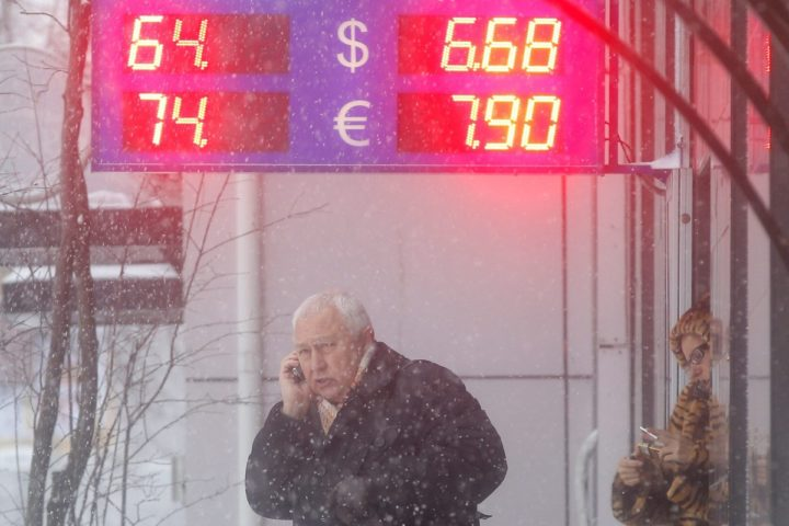 2015-02-03 16:29:03 epa04602083 A man walks in front of a currency exchange office during snowfall in Moscow, Russia, 03 February 2015. The US dollar and euro dropped against Russian ruble 2,71 per cent and 2,49 per cent respectively from previous exchange rates mainly due to an essential increase of oil world prices. EPA/MAXIM SHIPENKOV