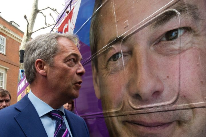 Leader of the United Kingdom Independence Party (UKIP), Nigel Farage gazes at a large-scale image of his face on the side of the bus at the launch of the party's open-top bus that will be touring the UK for the campaign to leave the European Union, ahead of the referendum, in London on May 20, 2016. The referendum for whether Great Britain stays in or leaves the EU will take place on June 23. / AFP PHOTO / JUSTIN TALLIS