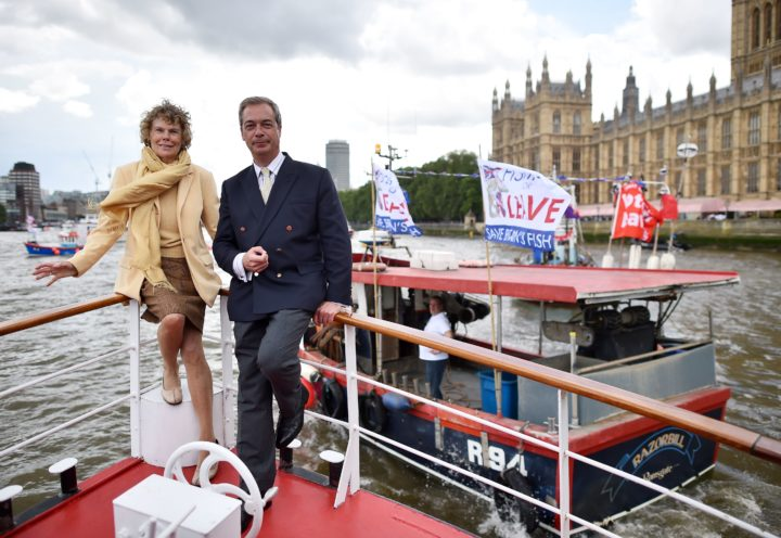 2016-06-15 12:32:56 UK Independence party leader Nigel Farage (R) and Labour party MP Kate Hoey pose on a passenger boat as they accompany a Brexit flotilla of fishing boats on the river Thames past the Houses of Parliament in London on June 15, 2016. A Brexit flotilla of fishing boats sailed up the River Thames into London today with foghorns sounding, in a protest against EU fishing quotas by the campaign for Britain to leave the European Union. / AFP PHOTO / BEN STANSALL