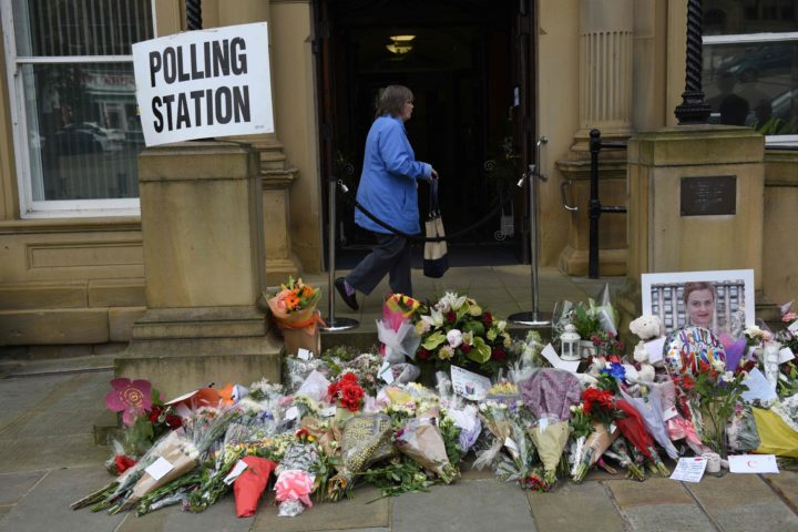 2016-06-23 12:07:12 A woman passes floral tributes to murdered MP Jo Cox outside Batley Town Hall as she arrives to vote in the EU referendum in Batley, northern England on June 23, 2016. Millions of Britons began voting today in a bitterly-fought, knife-edge referendum that could tear up the island nation's EU membership and spark the greatest emergency of the bloc's 60-year history. / AFP PHOTO / OLI SCARFF