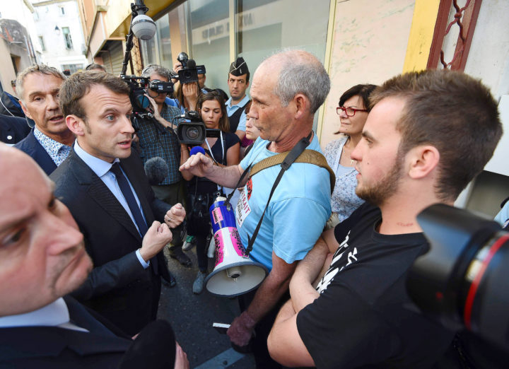2016-05-27 17:32:15 French Economy Minister Emmanuel Macron (L) speaks with protesters about the controversial government's labour reform, during a visit in Lunel on May 27, 2016. / AFP PHOTO / SYLVAIN THOMAS