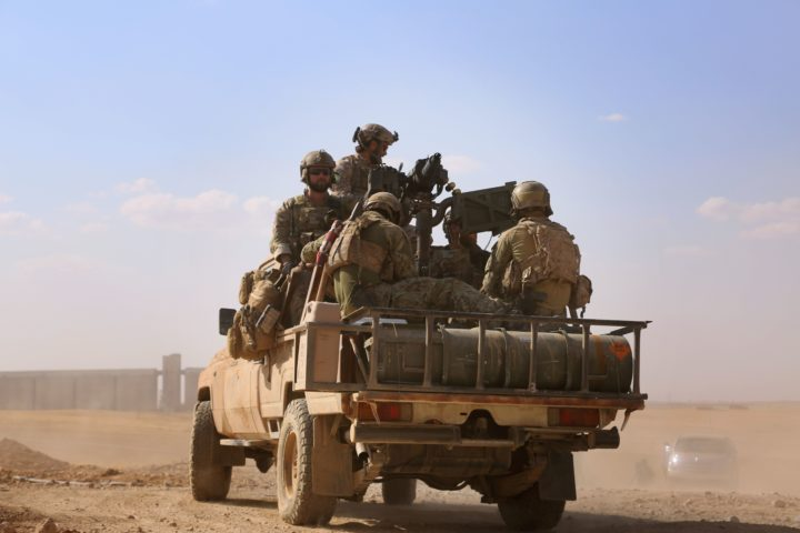 2016-05-25 16:16:13 Armed men in uniform identified by Syrian Democratic forces as US special operations forces ride in the back of a pickup truck in the village of Fatisah in the northern Syrian province of Raqa on May 25, 2016. US-backed Syrian fighters and Iraqi forces pressed twin assaults against the Islamic State group, in two of the most important ground offensives yet against the jihadists. The Syrian Democratic Forces (SDF), formed in October 2015, announced on May 24 its push for IS territory north of Raqa city, which is around 90 kilometres (55 miles) south of the Syrian-Turkish border and home to an estimated 300,000 people. The SDF is dominated by the Kurdish People's Protection Units (YPG) -- largely considered the most effective independent anti-IS force on the ground in Syria -- but it also includes Arab Muslim and Christian fighters. / AFP PHOTO / DELIL SOULEIMAN