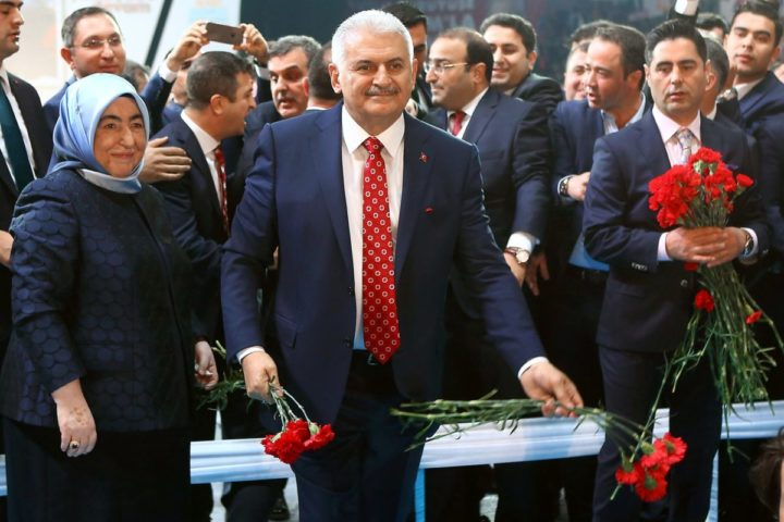 2016-05-22 22:55:40 Turkey's Minister of Transport, Maritime and Communication and new chairman candidate for ruling AK Party Binali Yildirim (C), flanked by wife Semiha Yildirim (L), holds red carnations before throwing them to supporters as he arrives for the second extraordinary congress of the AK Party at the Ankara Arena in Ankara, on May 22, 2016. Turkey's Transport Minister Binali Yildirim is set to be appointed head of the ruling party and the country's new prime minister, consolidating strongman President Recep Tayyip Erdogan's grip on power. / AFP PHOTO / ADEM ALTAN