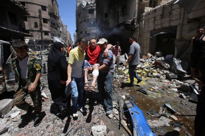 2016-06-11 13:20:31 Syrians carry a wounded man at the scene of a double bombing attack on June 11, 2016 outside the Sayyida Zeinab shrine, which is revered by Shiites around the world, some ten kilometres south of the centre of Damascus. The official SANA news agency said a suicide bomber and a car bomb struck at the entrance to the shrine. / AFP PHOTO / YOUSSEF KARWASHAN