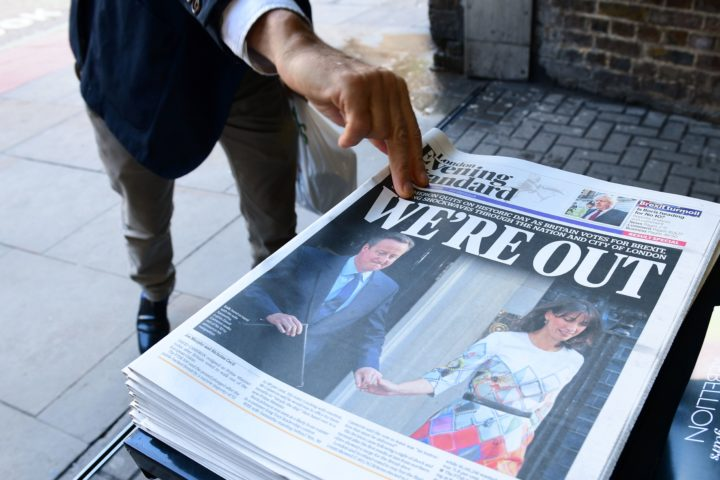2016-06-24 13:10:45 TOPSHOT - A man takes a copy of the London Evening Standard with the front page reporting the resignation of British Prime Minister David Cameron and the vote to leave the EU in a referendum, showing a pictured of Cameron holding hands with his wife Samantha as they come out from 10 Downing Street, in London on June 24, 2016. Britain voted to break away from the European Union on June 24, toppling Prime Minister David Cameron and dealing a thunderous blow to the 60-year-old bloc that sent world markets plunging. / AFP PHOTO / LEON NEAL