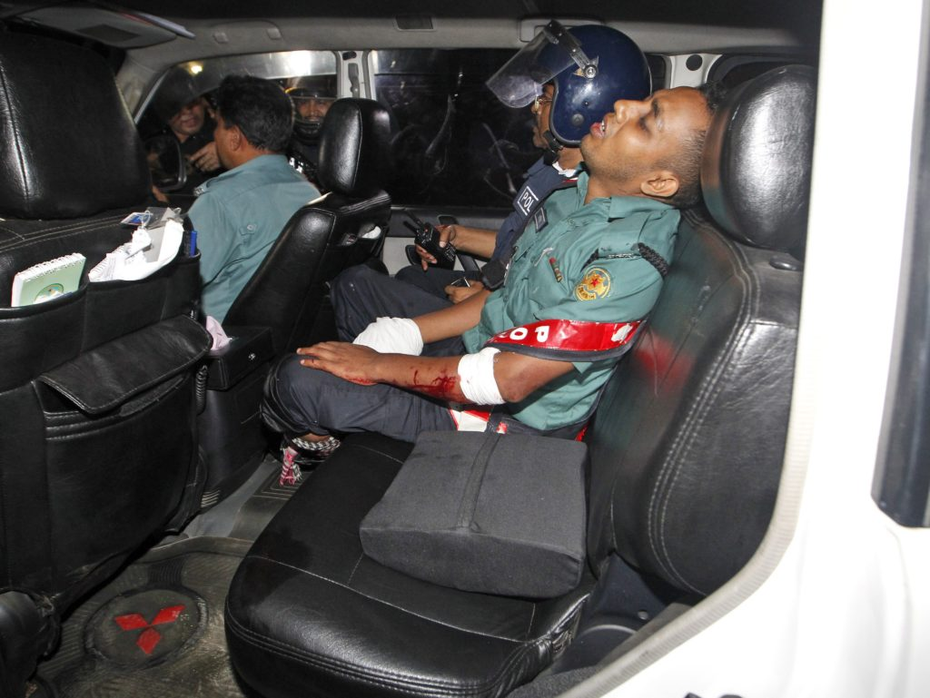 epa05402230 An injured police officer sits in a car after suffering wounds from a crude bomb blasted by suspected criminals at a Spanish resturant in Dhaka, Bangladesh, late 01 July 2016. Two police officials have been killed during the encounter while some gunmen reportedly took several people hostage, including some foreigners, inside a Spanish resturant. The law inforcement officials try to negotiate with the gunmen while the US-based SITE Intelligence Group quoted the Amaq News Agency as saying that fighters of the terrorist organisation 'Islamic State' (IS) carried out the attack. EPA/STRINGER