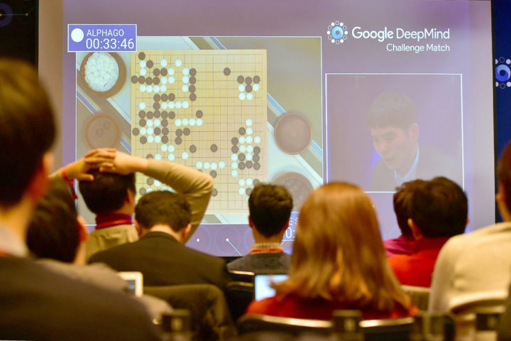 """2016-03-12 07:34:10 Journalists watch a big screen showing live footage of the third game of the Google DeepMind Challenge Match between Lee Se-Dol, one of the greatest modern players of the ancient board game Go, and the Google-developed supercomputer AlphaGo at a hotel in Seoul on March 12, 2016. A Google-developed computer programme took an unassailable 3-0 lead in its match-up with a South Korean Go grandmaster on March 12 -- marking a major breakthrough for a new style of """"intuitive"""" artificial intelligence (AI). / AFP PHOTO / JUNG Yeon-Je"""