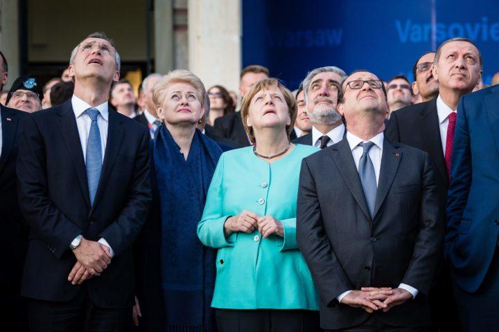 NAVO-leiders kijken omhoog naar overvliegende gevechtsvliegtuigen voorafgaand aan de Warschau-bijeenkomst - Foto: AFP
