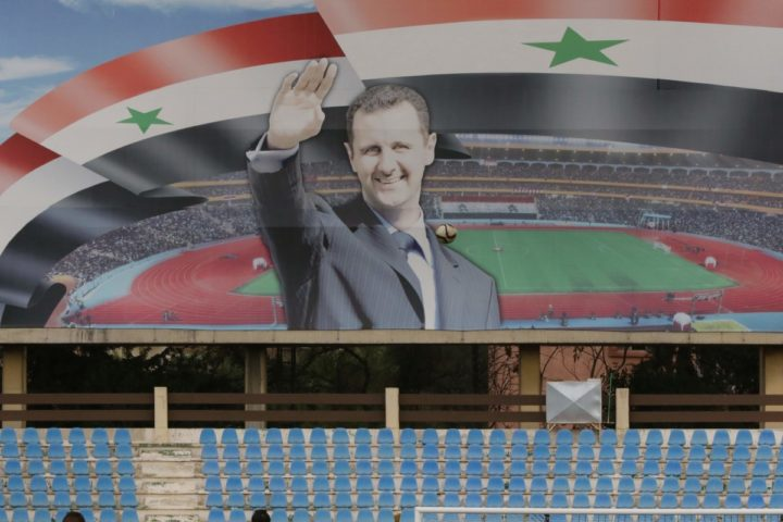 2016-03-04 15:23:40 A poster of Syrian President Bashar al-Assad is seen during a football game between Latakia's Hutteen and Hama's Taliya as part of the Syrian league at the Tishreen Sport City Stadium in Damascus on March 4, 2016. / AFP / LOUAI BESHARA / TO GO WITH AFP STORY BY FAYEZ WEHBE
