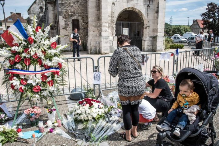 epa05445434 People pay tribute at a makeshift memorial in front of the Saint Etienne church where Priest Jacques Hamel was killed on 26 July in a terror related attack, in Saint-Etienne-du-Rouvray, near Rouen, 28 July 2016. The two hostage takers were killed by police after they took five hostages and killed Priest Jacques Hamel. EPA/CHRISTOPHE PETIT TESSON