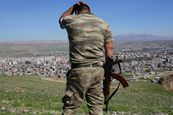 2016-03-02 11:44:01 TOPSHOT - A Turkish soldier gestures while standing on the hill overlooking damaged buildings following heavy fighting between government troops and Kurdish fighters in the Kurdish town of Cizre in southeastern Turkey, which lies near the border with Syria and Iraq, on March 2, 2016.  Thousands in Turkey's Kurdish-majority town of Cizre started returning to their homes on March 2 after authorities partially lifted a curfew in place since December for a controversial military operation to root out separatist rebels.  / AFP / YASIN AKGUL