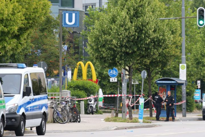 2016-07-23 00:00:00 epa05437457 Police officers stand near a police line blocking the area near a McDonald's fast food restaurant in Munich, Germany, 23 July 2016, after a shootout on the previous day. According to authorities, at least 10 people died, including the suspect, and 16 were hospitalized after a shooting at the Olympia shopping centre in Munich on 22 July 2016. By the current status of the investigations, the perpetrator, an 18-year-old German-Iranian from Munich, had apparently acted alone, police said. The motive of the incident is yet unclear. EPA/KARL-JOSEF HILDENBRAND