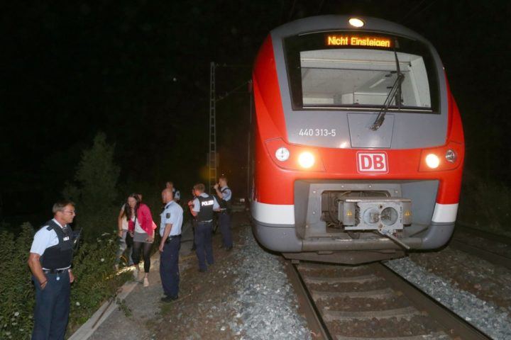epa05431115 Police stand by the regional train on which a man allegedly wielding an axe attacked passengers in Wuerzburg, Germany, 18 July 2016. Reports state that a man allegedly wielding an axe injured multiple passengers on a regional train in Wuerzburg. The attacker was shot by police. EPA/Karl-Josef Hildenbrand