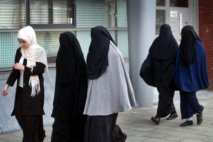 2003-03-07 00:00:00 NLD-20030307-UTRECHT: Vrouwen met gezichtssluiers (burka) komen vrijdag aan in Utrecht voor een openbare zitting van de Commissie Gelijke Behandeling. Twee meisjes van het Regionaal Opleidingen Centrum (ROC) in Amsterdam stapten naar de Commissie omdat het ROC in januari een verbod afkondigde op het dragen van de sluier. ANP FOTO/ROBERT VOS