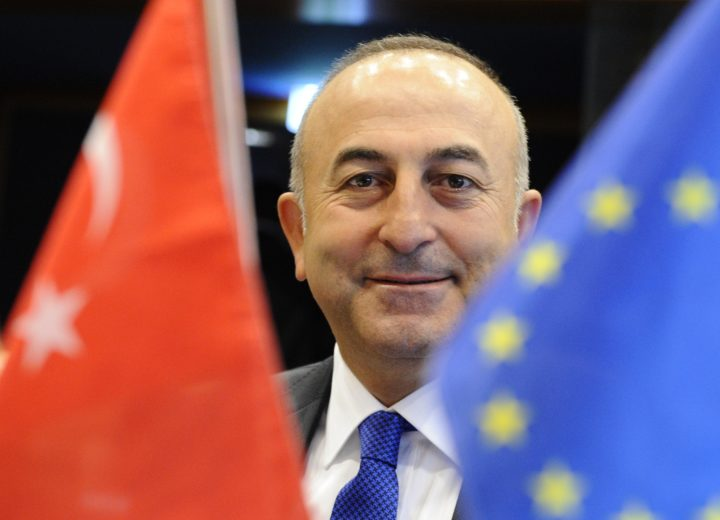 2014-06-23 07:57:55 (FILES) This file picture dated on June, 23 2014 shows Turkey's European Union (EU) Affairs Minister Mevlut Cavusoglu smiling between a Turkey national flag (L) and an EU flag, before taking part in the EU-Turkey Association Council meeting in Luxembourg. Turkish Prime Minister Ahmet Davutoglu announced on August 29, 2014 his new government after Recep Tayyip Erdogan took the presidency, with former Europe minister Mevlut Cavusoglu promoted to foreign minister. AFP PHOTO/JOHN THYS