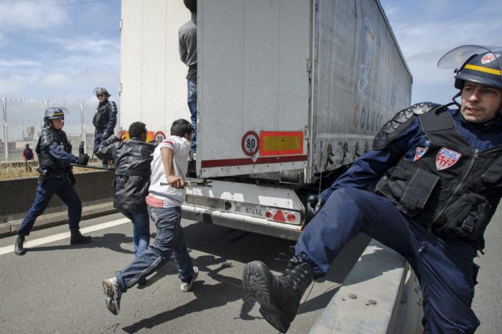 2015-06-18 00:00:00 CALAIS - Vluchtelingen gaan de laadruimte binnen van een vrachtwagen die op weg is naar de veerboot, terwijl agenten proberen dat te verhinderen. Maatregelen zoals het plaatsen van hekken moeten voorkomen dat migranten zich in laadruimtes verschuilen in een poging Engeland te bereiken. ANP MARTEN VAN DIJL