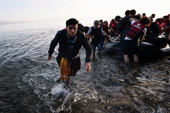 2015-08-15 10:27:09 Syrian migrants arrive on an overcrowded a dinghy on a beach near the port on the Greek island of Kos on August 15, 2015. A ferry boat has been sent by the Greek government to the resort of Kos to speed up the registration process of hundreds of Syrian refugees, docked on August 14 afternoon at the harbour. The Eleftherios Venizelos will stay moored in Kos for some two weeks, during which time authorities will register newcomers to the island, which is already overflowing with refugees and migrants. AFP PHOTO /LOUISA GOULIAMAKI