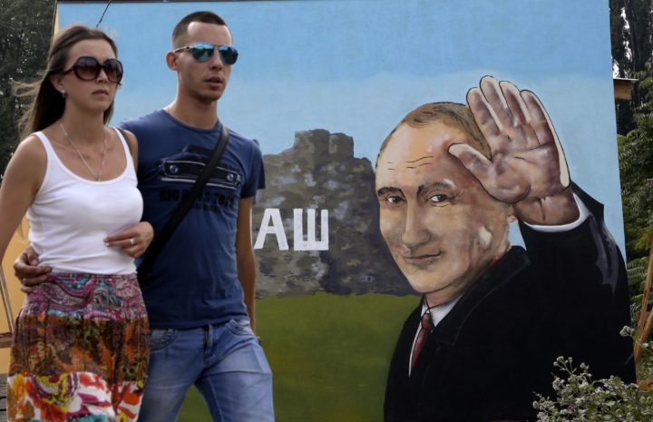2015-08-18 10:55:51 A couple walks past a graffito depicting Russia's President Vladimir Putin in the Crimean city of Simferopol on August 18, 2015. AFP PHOTO / MAX VETROV