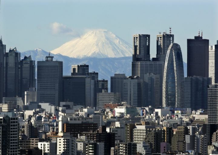 2016-01-20 11:10:11 epa05112459 Snow-covered peak of Mount Fuji is seen through Shinjuku skyscrapers in Tokyo, Japan, 20 January 2016. Japan's parliament enacted on 20 Janaury 2016 the 3.32 trillion yen (about 28.2 billion US dollars) extra budget for 2015 fiscal year to bolster Japanese economy after approved by the Upper House. EPA/KIMIMASA MAYAMA