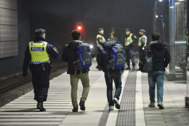 epa05131193 A picture made available 28 January 2016 shows a Swedish policeman escorting asylum-seeking refugees from a train at Hyllie station outside Malmoe, Sweden, 17 December 2015. Sweden is preparing for the expulsion of up to 80,000 people whose asylum bids have been rejected, a cabinet member said 28 January 2016. A record 163,000 people applied for asylum in Sweden in 2015, straining resources and capacity at reception centres and local municipalities. The increase of explusions will be likely only at the beginning of 2017 though, due to the backlog the Swedish Migration Agency was struggeling with. EPA/JOHAN NILSSON SWEDEN OUT
