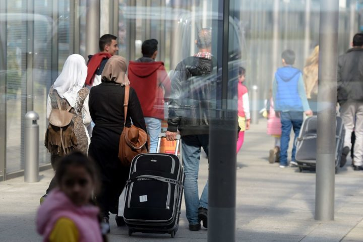 2016-04-04 12:58:38 Syrian refugees walk past a hall after landing at Hanover airport, central Germany, on April 4, 2016. The first Syrians arrived in Germany from Istanbul under a controversial EU-Turkey migrant pact. / AFP PHOTO / TOBIAS SCHWARZ