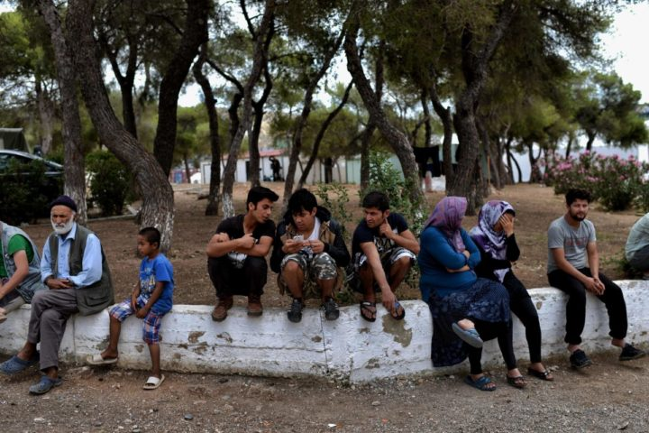 2016-06-08 11:36:38 TO GO WITH AFP STORY BY JOHN HADOULIS People sit on a low wall at the refugee and migrant camp of Schisto in Athens on June 8, 2016. Organisers in Greece are taking steps to help thousands of migrants housed in the country's camps to celebrate Ramadan, but many say food and housing problems make it more difficult for them to practise the annual fast. Greek officials say those fasting are given their sundown meal together with the pre-dawn meal, which they can pack away and eat at their discretion. / AFP PHOTO / ARIS MESSINIS
