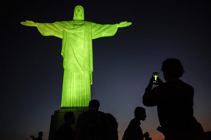 2016-08-04 21:37:48 TOPSHOT - Visitors stand under the Christ the Redeemer statue on Corcovado mountain ahead of the Rio 2016 Olympic Games in Rio de Janeiro on August 4, 2016. / AFP PHOTO / JEFF PACHOUD