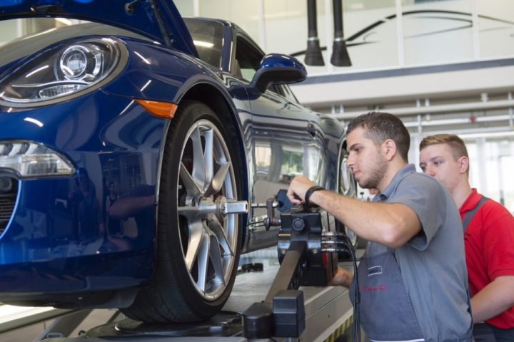 2016-07-27 09:17:47 Ammar Alkhouli (L), 19-year-old refugee from Syria, and German trainee Dennis Strohmaier work on a Porsche 911 Carrera S at the training center of Porsche AG in Stuttgart, southwestern Germany, on July 27, 2016. Alkhouli takes part at an Porsche integration programm. / AFP PHOTO / THOMAS KIENZLE