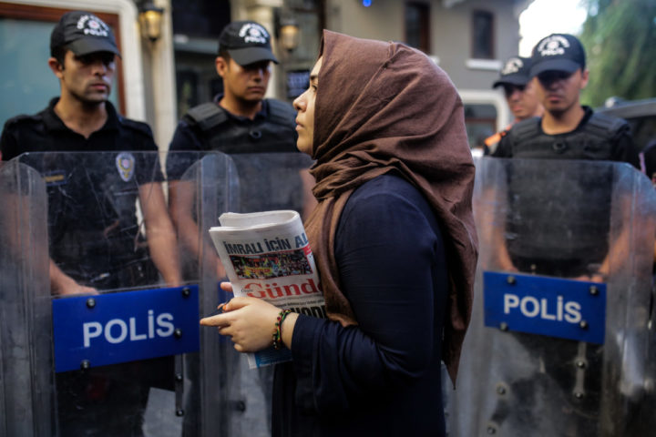"""2016-08-16 18:02:06 A woman holds a """"Ozgur Gundem"""" newspaper in front of a police barricade on August 16, 2016 in Istanbul. A Turkish court has ordered the temporary closure of a newspaper accusing it of links with Kurdish militants and spreading terrorist propaganda. / AFP PHOTO / YASIN AKGUL"""