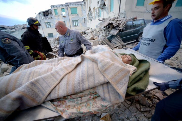 TOPSHOT - Rescues carry a man in Amatrice on August 24, 2016 after a strong heartquake. Central Italy was struck by a powerful, 6.2-magnitude earthquake in the early hours of Wednesday, which has killed at least three people and devastated dozens of mountain villages. Numerous buildings had collapsed in communities close to the epicenter of the quake near the town of Norcia in the region of Umbria, witnesses told Italian media, with an increase in the death toll highly likely. / AFP PHOTO / FILIPPO MONTEFORTE