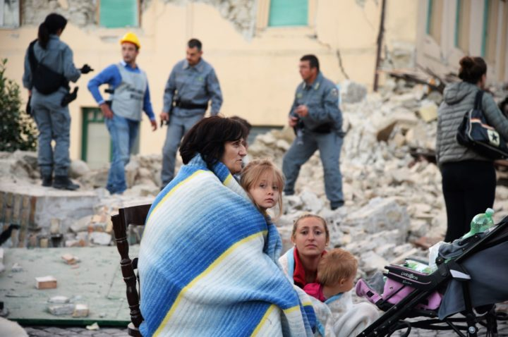 2016-08-24 04:29:09 TOPSHOT - Victims sit among the rubble of a house after a strong heartquake hit Amatrice on August 24, 2016. Central Italy was struck by a powerful, 6.2-magnitude earthquake in the early hours, which has killed at least three people and devastated dozens of mountain villages. Numerous buildings had collapsed in communities close to the epicenter of the quake near the town of Norcia in the region of Umbria, witnesses told Italian media, with an increase in the death toll highly likely. / AFP PHOTO / FILIPPO MONTEFORTE