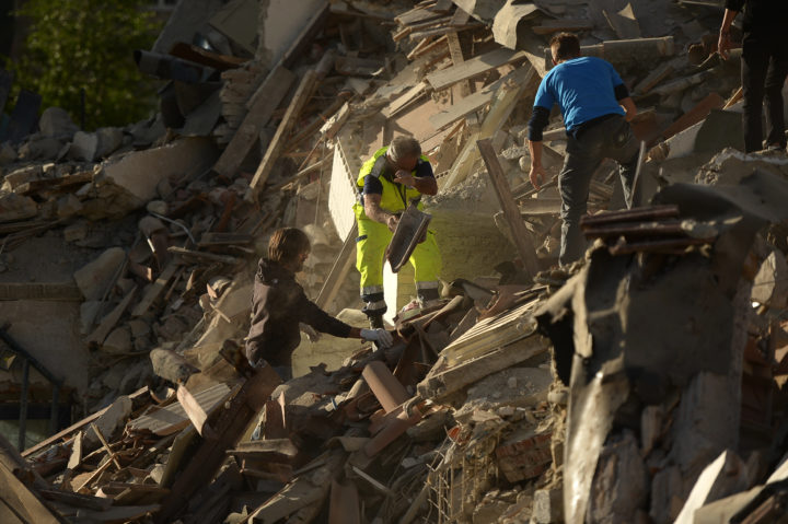 Resucers and residents clear debris in search for victims in damaged homes after a strong heathquake hit Amatrice on August 24, 2016. Central Italy was struck by a powerful, 6.2-magnitude earthquake in the early hours, which has killed at least three people and devastated dozens of mountain villages. Numerous buildings had collapsed in communities close to the epicenter of the quake near the town of Norcia in the region of Umbria, witnesses told Italian media, with an increase in the death toll highly likely. / AFP PHOTO / FILIPPO MONTEFORTE