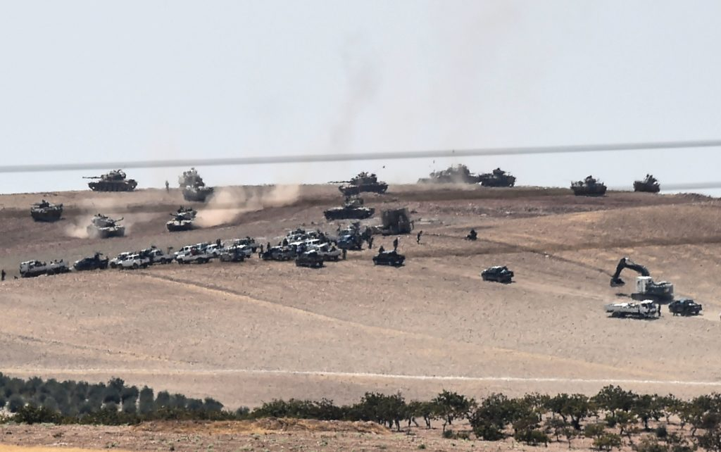 2016-08-24 05:57:13 This picture taken from the Turkish Syrian border city of Karkamis in the southern region of Gaziantep, on August 24, 2016 shows Turkish army tanks and alleged Syrian opposition fighter trucks positioned two kilometres west from the Syrian Turkish border town of Jarabulus, preparing to move position. Turkey's army backed by international coalition air strikes launched an operation involving fighter jets and elite ground troops to drive Islamic State jihadists out of a key Syrian border town. The air and ground operation, the most ambitious launched by Turkey in the Syria conflict, is aimed at clearing jihadists from the town of Jarabulus, which lies directly opposite the Turkish town of Karkamis. / AFP PHOTO / BULENT KILIC