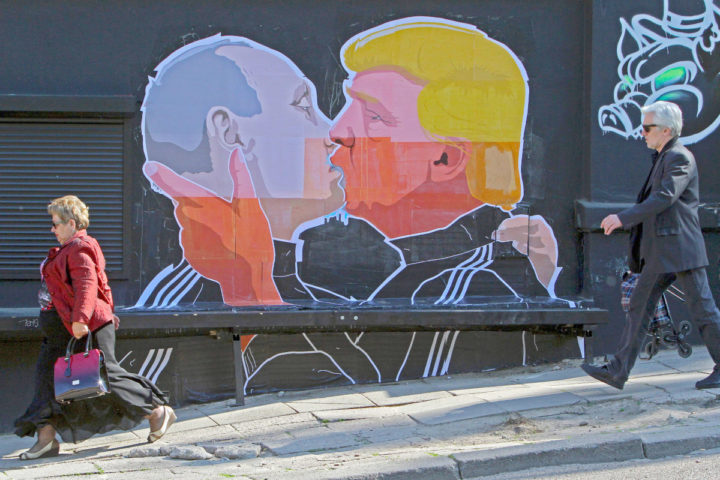 2016-05-13 09:54:56 TOPSHOT - People walk past a mural on a restaurant wall depicting US Presidential hopeful Donald Trump and Russian President Vladimir Putin greeting each other with a kiss in the Lithuanian capital Vilnius on May 13, 2016. Kestutis Girnius, associate professor of the Institute of International Relations and Political Science in Vilnius university, told AFP -This graffiti expresses the fear of some Lithuanians that Donald Trump is likely to kowtow to Vladimir Putin and be indifferent to Lithuania's security concerns. Trump has notoriously stated that Putin is a strong leader, and that NATO is 'obsolete and expensive.' / AFP PHOTO / Petras Malukas